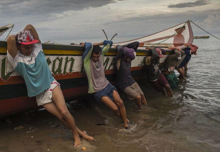 Pescadores de la familia Marval traen su bote a tierra después de pescar toda la noche, en Punta de Araya, estado Sucre, Venezuela. (AP/Rodrigo Abd)