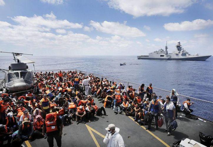 Imagen que muestra a varios inmigrantes trasladados de la fragata italiana 'Euro' al 'Virgilio Fasan' (derecha) dentro de la operación 'Mare Nostrum' en el sur del mar Mediterráneo. (Archivo/EFE)