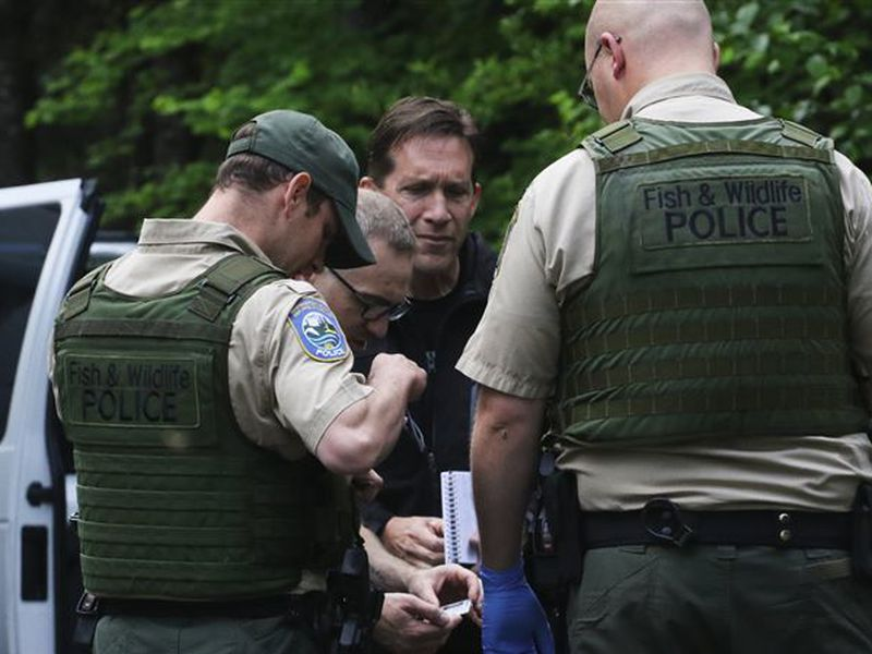 Washington State Fish and Wildlife Police confer with an individual, following a fatal cougar attack.