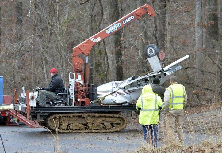 Trabajadores rescatan partes de la avioneta accidentada, en donde una niña de 7 años fue la única sobreviviente. (Agencias)