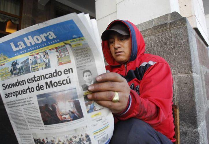 Un hombre lee un diario con el titular sobre Snowden en Moscú, en Quito, Ecuador. (Agencias)