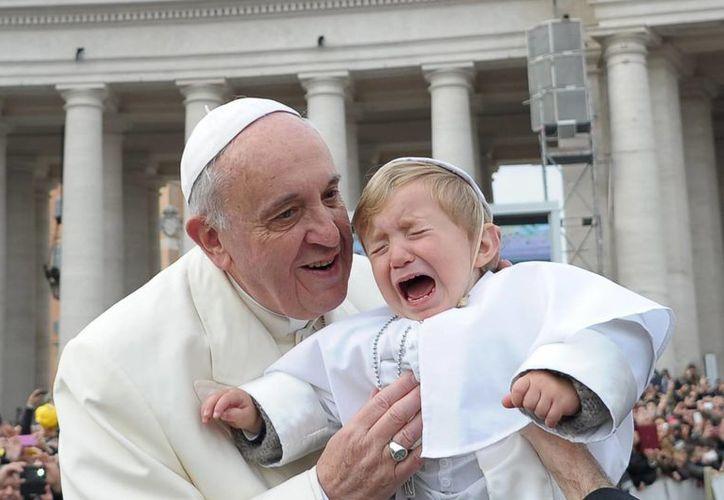 Francisco toma en sus brazos a Daniele De Sanctis, a quien disfrazaron como el pontífice para el Carnaval. (Agencias)
