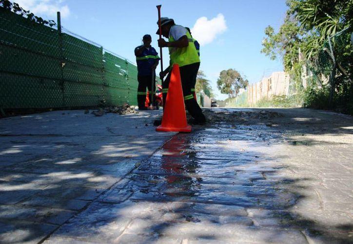Trabajadores de Aguakan se presentaron ayer para arreglar la fuga de agua en el acceso a Xcalacoco. (Octavio Martínez/SIPSE)