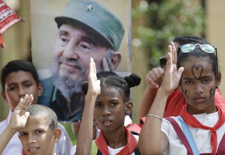 Niños en uniforme escolar saludan colocando el pulgar derecho en la frente al paso de las cenizas del líder cubano Fidel Castro en Santiago. (AP/Natacha Pisarenko)