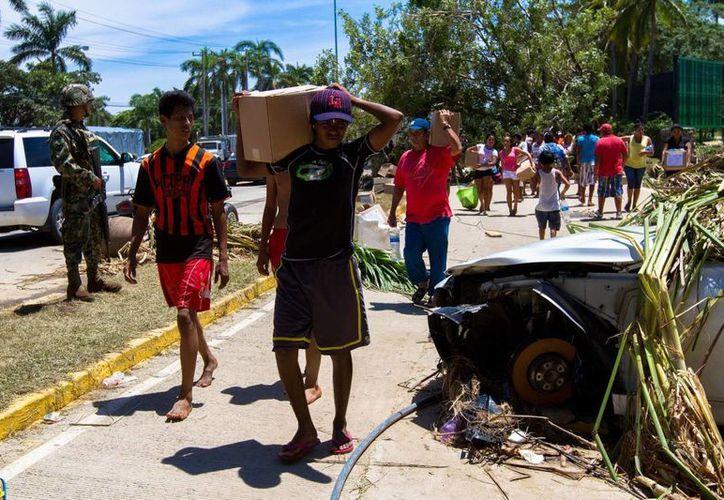 """Llega la ayuda humanitaria a los afectados por las lluvias a punta diamante en el """"Boulevard de Las Naciones"""". (Notimex)"""