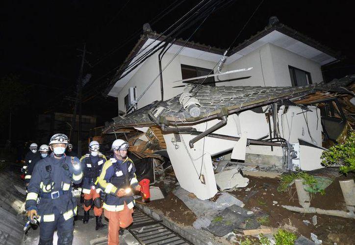 Bomberos verifican los daños de una casa derrumbada en Nashik, cerca de la ciudad de Kumamoto, el sur de Japón, tras el terremoto de la madrugada de este viernes. Reportan residentes atrapados en por lo menos dos docenas de casas que colapsaron después de un fuerte sismo de 6.5 grados  (Tomoaki Ito / Kyodo News a través de AP)