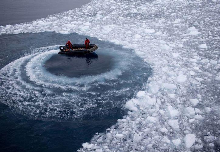 Agentes de la marina chilena apartan hielo moviendo su bote en círculos conforme se acercan al barco de la marina Aquiles, donde recogerán a científicos internacionales para llevarlos a la estación científica chilena Bernardo O'Higgins en Antártida. (Agencias)