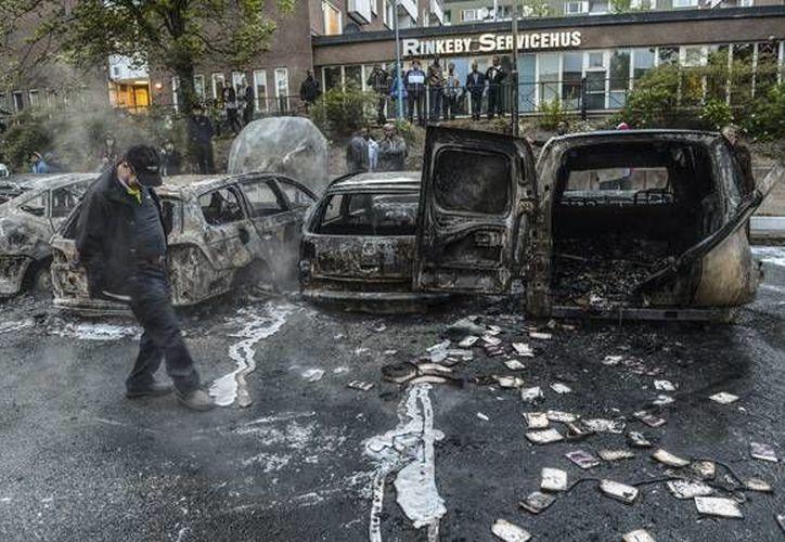 Jornada de disturbios en Suecia, luego de la detención de un hombre acusado de narcotráfico. Imagen de contexto de una persona mirando los vehículos incendiados por migrantes luego de una jornada de saqueos en Estocolmo. (Archiv/EFE)