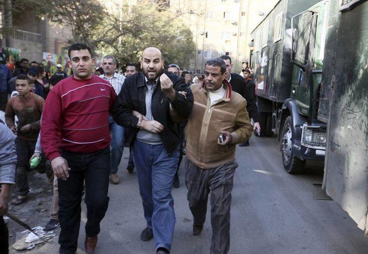 Dos policías detienen a un simpatizante de los Hermanos Musulmanes (c) durante unos disturbios ocurridos en El Cairo, Egipto. (Archivo/EFE)