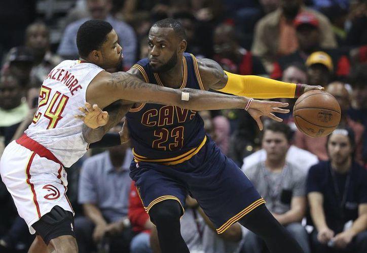 Cavaliers de Cleveland, con LeBron James al mando, enfrentarán a Hawks de Atlanta en la segunda ronda de playoffs de NBA. En la foto, LeBron James (c) contra Kent Bazemore. (AP)