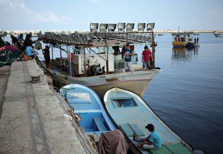 Niños palestinos juegan en un bote pesquero mientras los pescadores aprestan sus redes en el puerto de Ciudad Gaza. (Agencias)