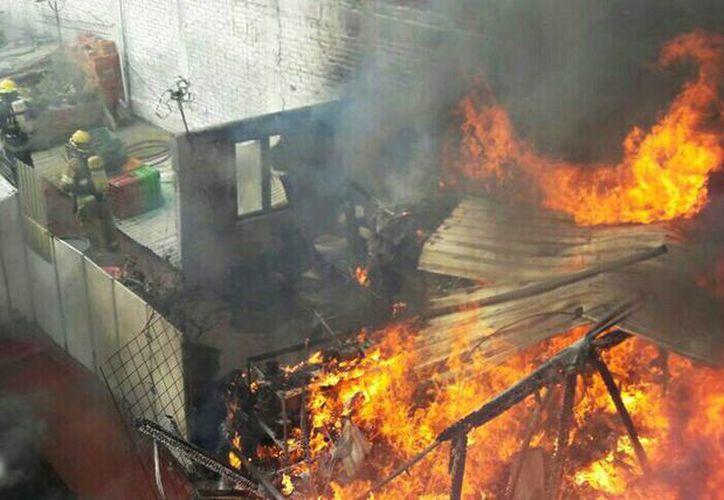 Un incendio consumió una bodega y tres vehículos que estaban estacionados cerca del lugar, cerca de la autopista Siglo XXI en Arteaga, Michocán. (moreliactiva.com)