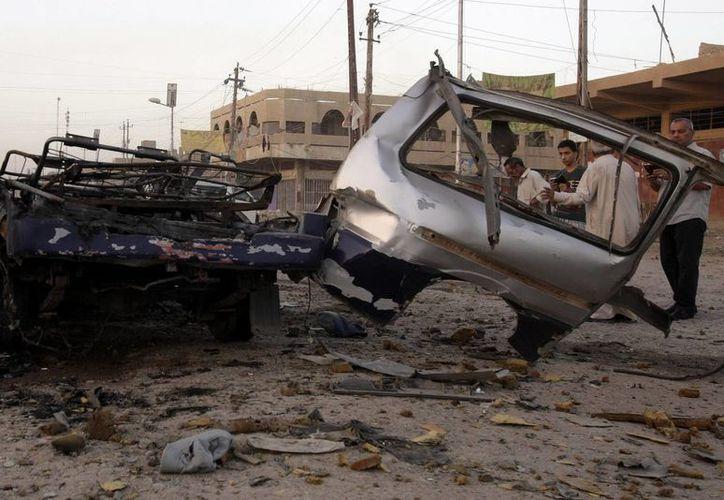Varios ciudadanos iraquíes observan el lugar donde se produjo el atentado de un coche bomba, en la localidad de Husseiniya. (EFE)