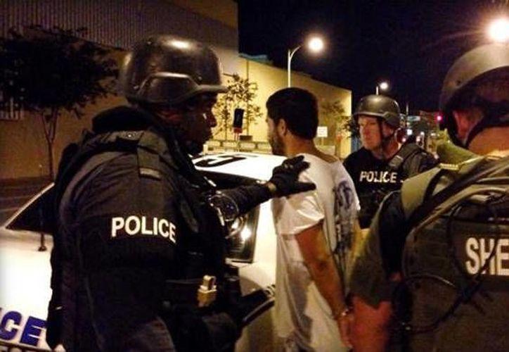 Oficiales del Departamento de la Policía de Tampa y la Oficina del Sheriff del Condado de Pasco al momento de llevar a Adam Matos hacia la patrulla. (Departamento de la Policía de Tampa/cbsnews.com)
