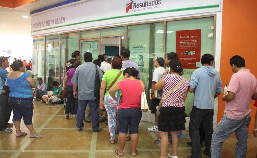 Las largas filas causan molestias a los ciudadanos. (Sergio Orozco/SIPSE)