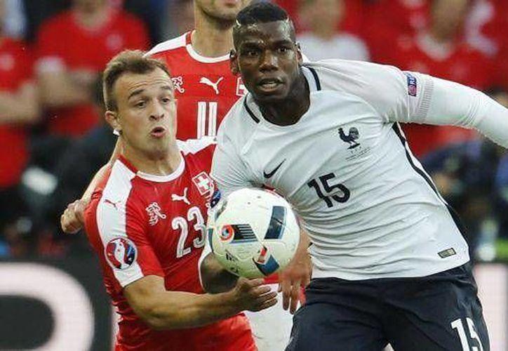 Francia y Suiza empataron 0-0 en gris partido de la fase de grupos de la Eurocopa. En la foto, el galo Paul Pogba (c) va por el balón ante el acoso de un jugador suizo. (elcomercio.pe)