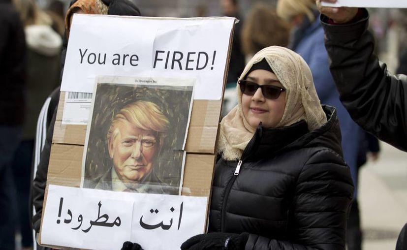 Una mujer protesta contra Donald Trump frente a la Casa Blanca en Washington este domindo. El fiscal de Washington dijo que la demanda se realizará en un tribunal federal de Seattle. (AP Photo/Jose Luis Magana)