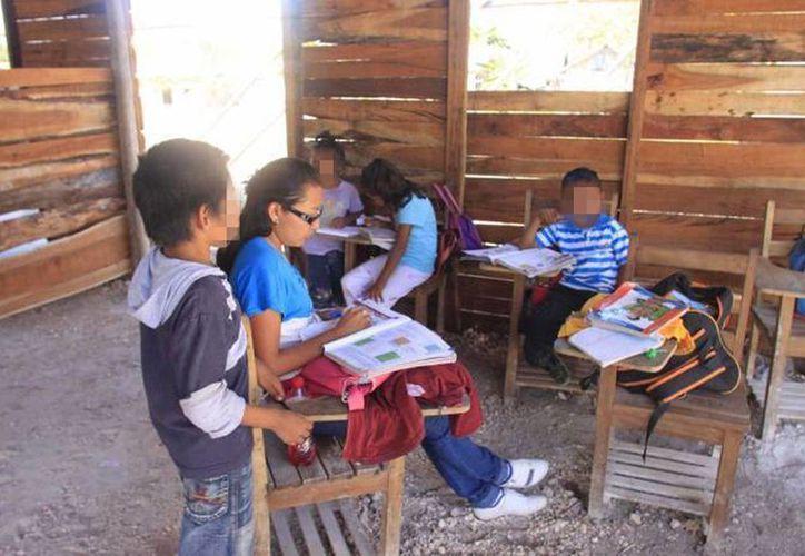 Asociaciones de padres de familia e igual número de líderes educativos recibieron cheques por 50 mil pesos para cada plantel. Imagen de una escuela rural en clase. (Archivo/SIPSE)