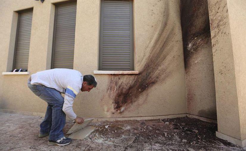 Yossi Haziza inspecciona los daños ocasionados por un cohete lanzado desde la franja de Gaza en su patio trasero en Sderot, Israel (EFE).