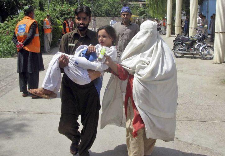 Un hombre lleva en brazos a una joven familiar, herida en el atentado perpetrado contra el colegio. (EFE)