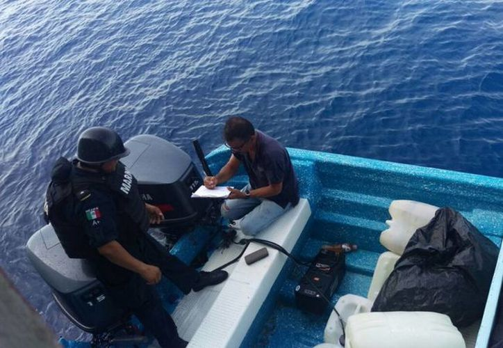 Momento en que personal naval asegura el cargamento de la presunta droga en una de las dos embarcaciones interceptadas en costas de Guerrrero. (Notimex)
