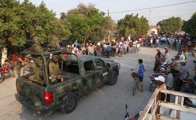 Cientos de soldados del ejército mexicano ingresan al poblado de Michoacan. (Agencias)