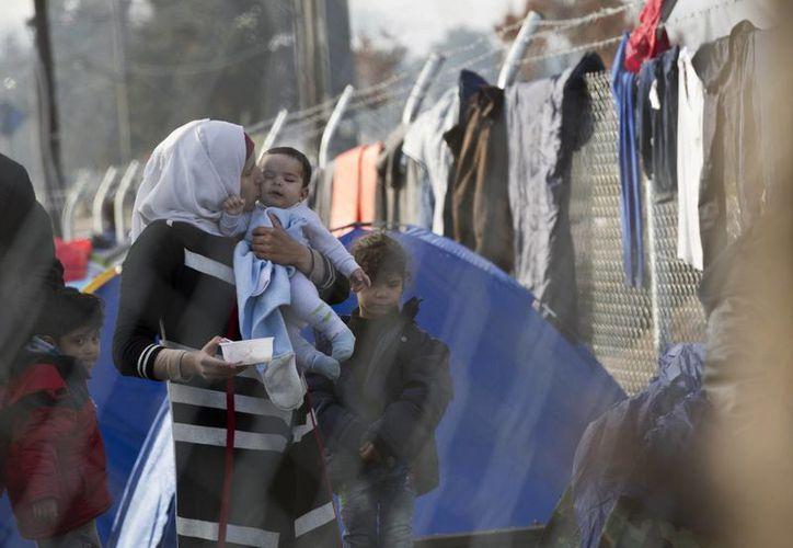 Una madre migrante sostiene a su bebé en brazos mientras esperan en el lago griego de la frontera entre Grecia y Macedonia para cruzar al país. (Agencias)