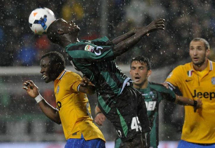 El ghanés Yussif Chibsah (d), del Sassuolo, compite por el balón con su compatriota Kwadwo Asamoah, de la Juve. (Foto: AP)