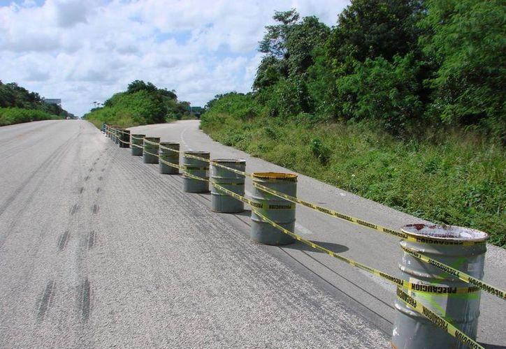 La Secretaría de Comunicaciones y Transportes colocó tambos y cintas de prevención, a efecto de que los usuarios de la vía federal continúen transitando por la carretera hasta ingresar a la ciudad. (Manuel Salazar/SIPSE)