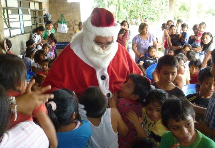 Vestido como Santa Claus, Joaquín Paredes Polanco reparte juguetes en la Navidad del año pasado. (Cortesía)