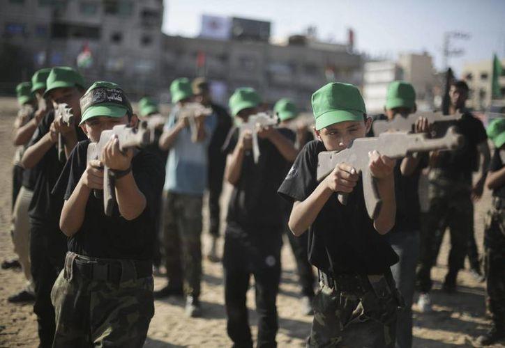 Unos niños palestinos practican en clase de tiro durante un entrenamiento militar. (Archivo/EFE)