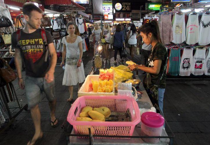Turistas caminan por un mercado después de que el toque de queda se levantara en Bangkok. (Agencias)
