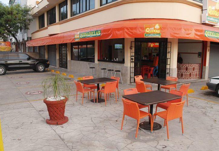 Las mesas que se colocan fuera de los negocios con frecuencia impiden el libre tránsito de los peatones por la zona del local. (Juan Estrada/SIPSE)