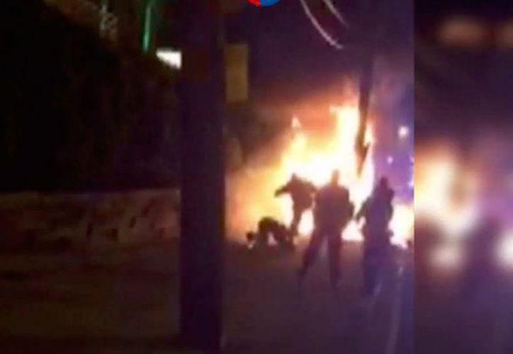 Un hombre con su ropa en llamas que rueda por el piso para tratar de apagarlas pero que es pateado por varios agentes. (Foto: Excélsior)
