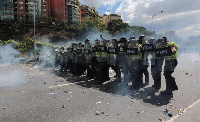 policías que usaron gases lacrimógenos y balas de goma para dispersar a un grupo que intentaba bloquear la principal autopista de Caracas. (AP/Fernando Llano)