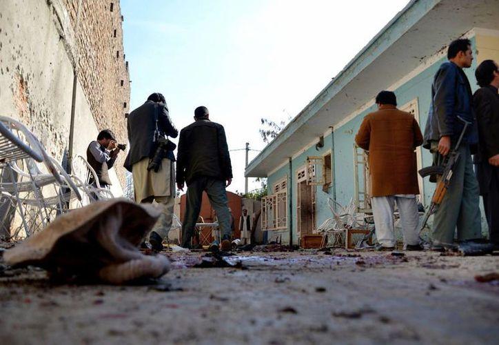 Agentes de seguridad inspeccionan cerca del lugar del atentado suicida dentro de una residencia en Jalalabad, Afganistán, el domingo 17 de enero de 2016. (AP/Mohammad Anwar Danishyar)