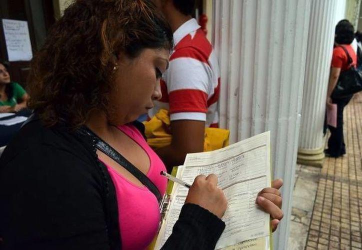 Una mujer llena una solicitud de trabajo donde existe una gran probabilidad que encuentre empleo en las llamadas outsourcing. (Archivo/SIPSE)