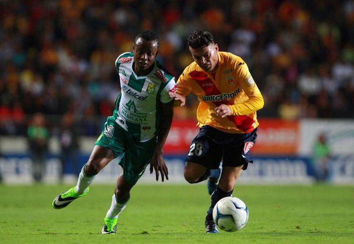 Carlos Morales (Morelia) y Eisner Loboa (León) durante el juego de ida de la liguilla del Torneo Apertura 2013 de la Liga MX en el estadio Morelos. El partido terminó empatado a tres goles. (Agencias)