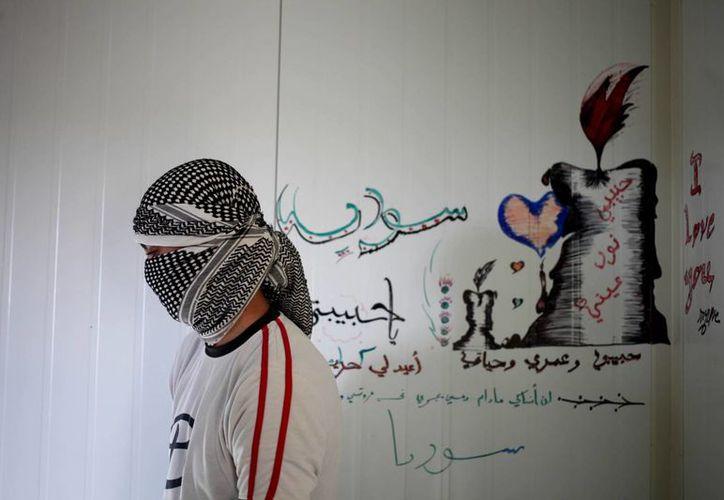 Joven en un campo de refugiados en la frontera de Siria. Detrás de él se lee: 'mi amor, mi vida, Siria'. (Agencias)