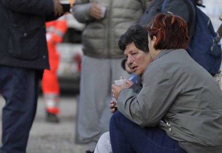 Un grupo de personas bebe en un asentamiento con tiendas de campaña cerca de Pescara Del Tronto, en el centro de Italia, tras el devastador sismo de magnitud 6 que arrasó la localidad. (AP/Andrew Medichini)