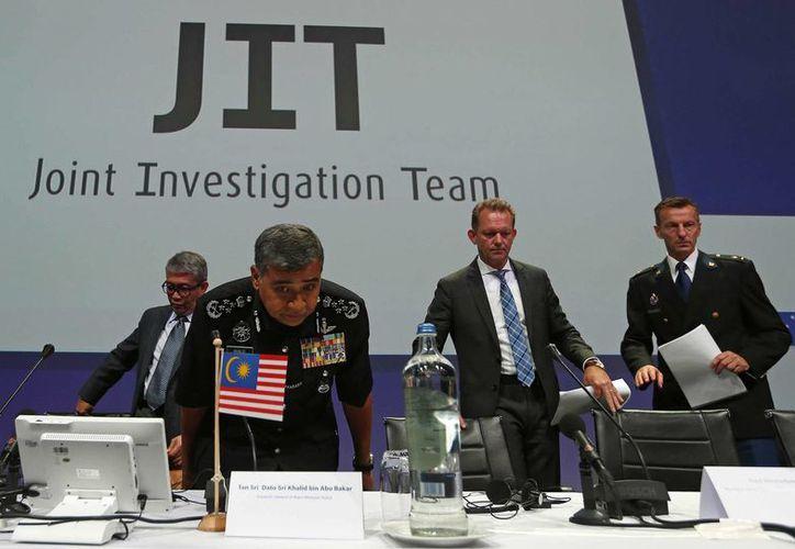 Tan Sri Dato' Sri Khalid Abu Bakar (c), Fred Westerbeke, segundo derecha y Wilbert Paulissen del Equipo Investigador Conjunto presentan los resultados preliminares de su investigación del jet de Malaysia Airlines MH17 derribado sobre Ucrania. (AP/Peter Dejong)