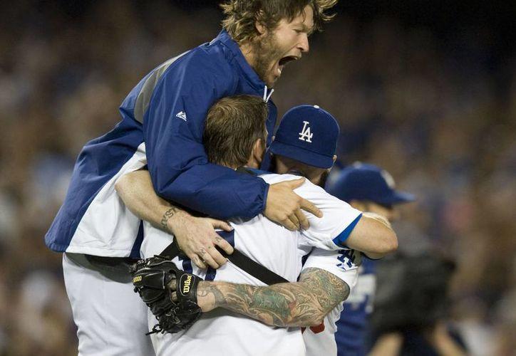 Clayton Kershaw (i) salta por sobre A.J. Ellis y Brian Wilson en el inicio de la celebración de Dodgers de Los Angeles. (Foto: AP)