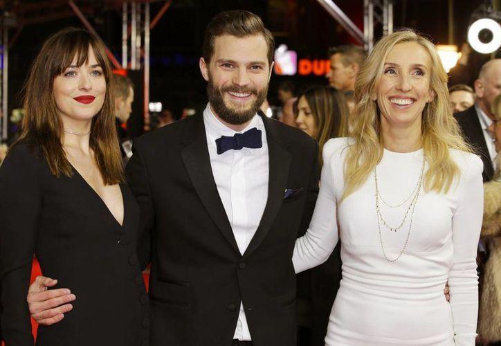 Los protagonistas de '50 shades of Grey', Dakota Johnson y Jamie Dornan, con el director Sam Taylor-Johnson en la muestra de cine del Festival de Berlín. (Foto: AP)