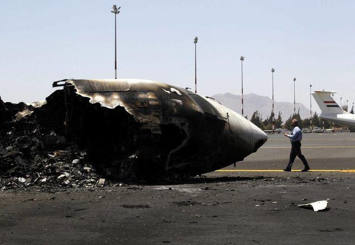 Un trabajador del aeropuerto pasa junto a un avión destrozado tras un ataque aéreo perpetrado por la coalición árabe liderada por Arabia Saudí en el aeropuerto internacional de Saná, Yemen. (Archivo/EFE)