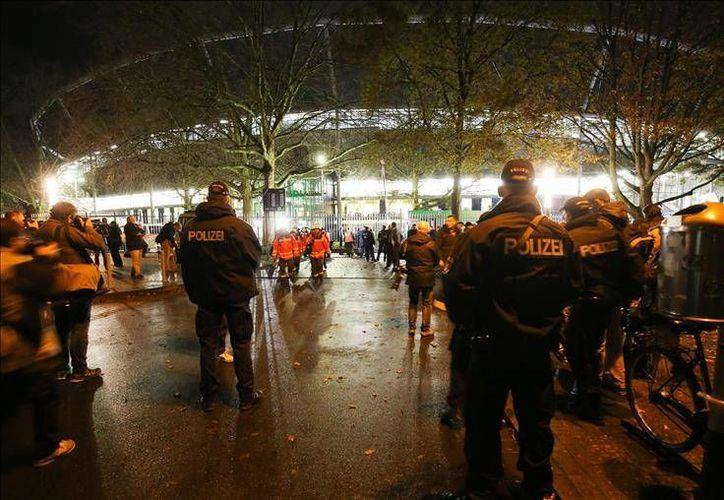 Policías alemanes permanecen afuera del estadio IDH Arena de Hannover después que se cancelara el encuentro amistoso entre las selecciones de Alemania y Holanda, previsto para este martes. (EFE)