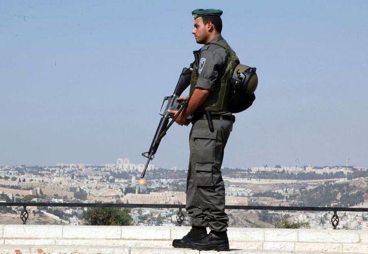Soldado israelí vigila desde lo alto la ciudad vieja de Jerusalén, escenario de enfrentamientos con palestinos; en el último mes, se han incremento los hechos de sangre. (AP)