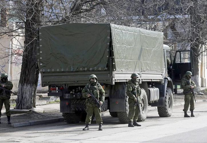 Hombres armados sin identificar vestidos con uniformes militares controlan una calle en el centro de Simferopol, Crimea, Ucrania. (EFE)