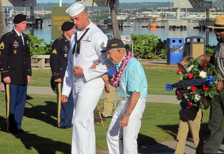 Un marinero de la Armada escolta al veterano de la Marina y Pearl Harbor superviviente John Chapman durante una ceremonia para conmemorar el 73º aniversario del ataque japonés a Pearl Harbor. (Agencias)