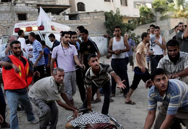 Palestinos auxilian a uno de los heridos en el ataque a una zona comercial de Shijaiya, en Gaza, en el que 16 personas murieron y unas 150 resultaron heridas. (AP)