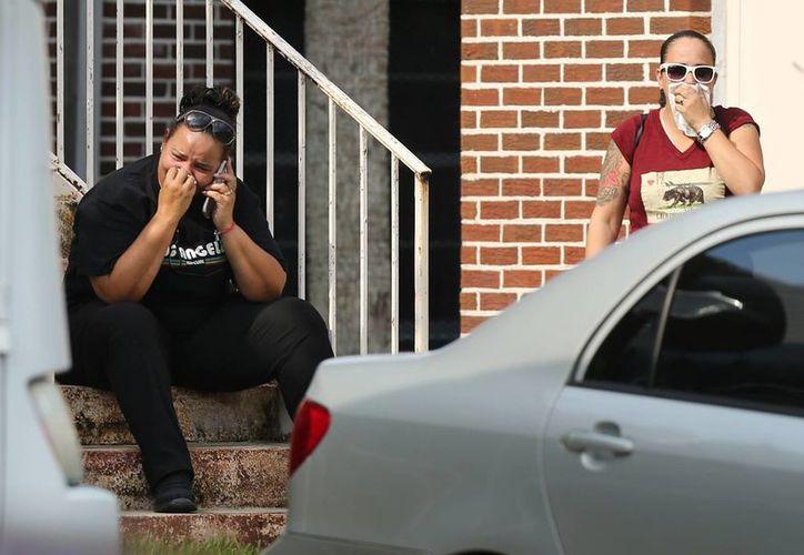 Familiares de las víctimas del ataque en un antro gay lloran afuera un centro comunitario donde agentes se encuentran dando información sobre el tiroteo que cobró la vida de 49 personas. (Agencias)